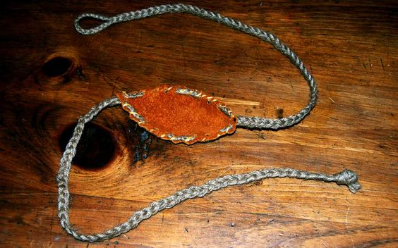 An orange leather pouch sling with two braided leads, one with a loop, the other ending in a knot.
