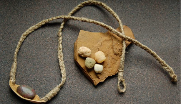 A stone rests in a sling made of leather with two braided leads; an open pouch with additional stones rests nearby.
