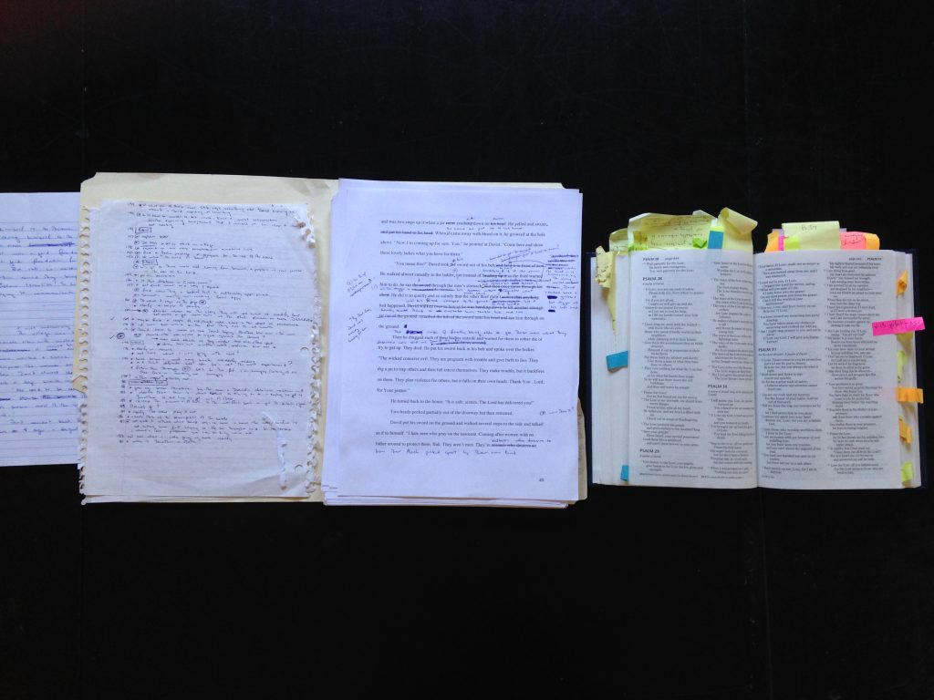 A line of marked-up research notes, manuscript pages, and a Bible full of post it flags.