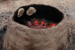bread baking on the inside walls of a replica of a biblical oven