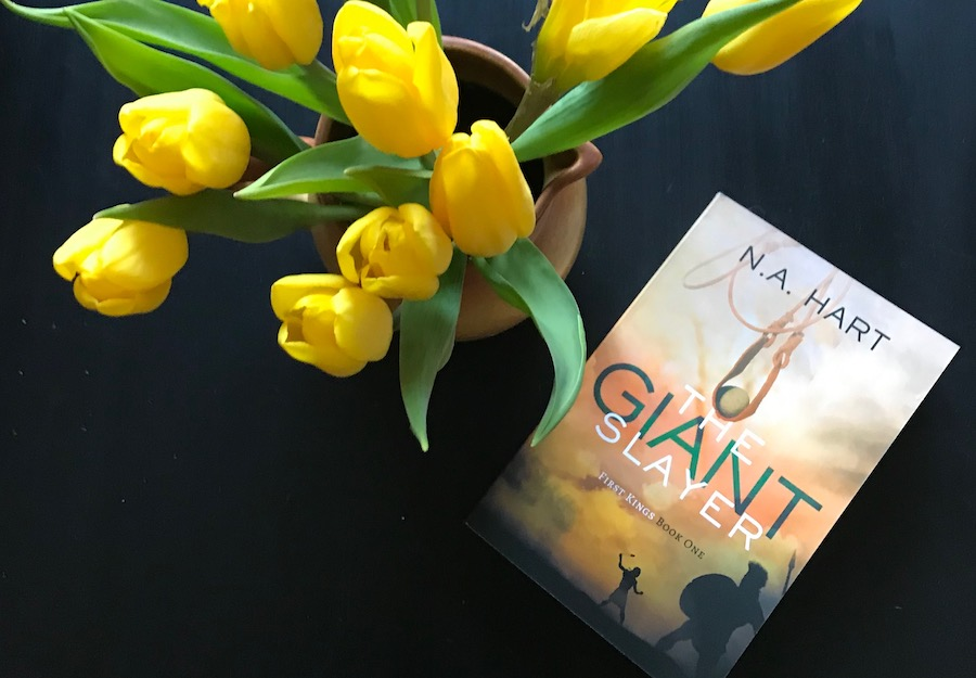 A bouquet of yellow tulips and the book The Giant Slayer on a black table.